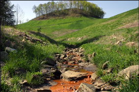 Arroyo contaminado por el escurrimiento de una mina de hierro a cielo abierto.